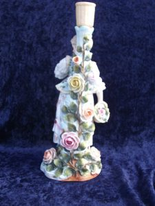This is the back of the figurine, showing more fabricated rose petals and vines.